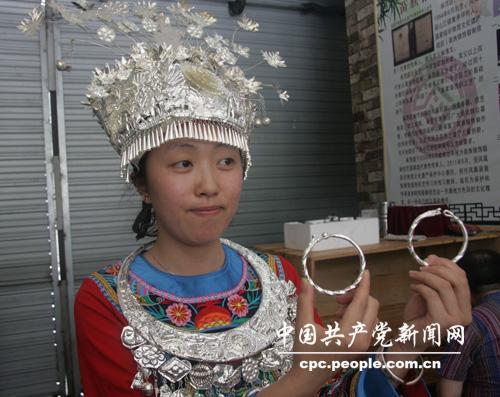 苗族姑娘展示锻造好的银手镯.记者赵晶