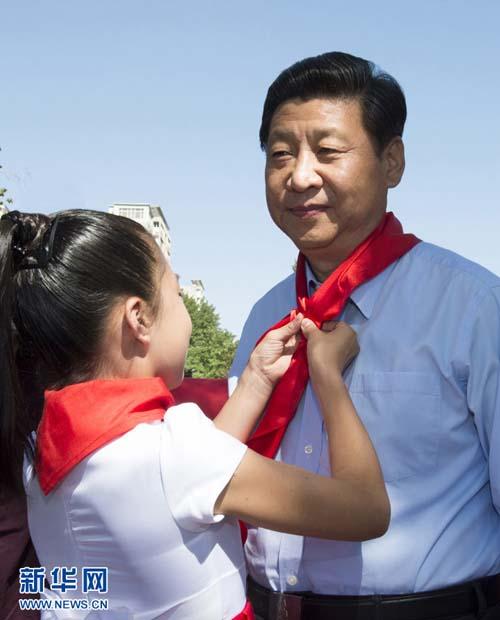 """5月29日,中共中央总书记、国家主席、中央军委主席习近平在北京市少年宫参加""""快乐童年放飞希望""""主题队日活动。这是少先队员为习近平佩戴上红领巾。 新华社记者李学仁摄"""