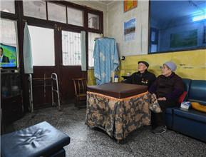张富清和老伴在住了几十年的老房子里看电视