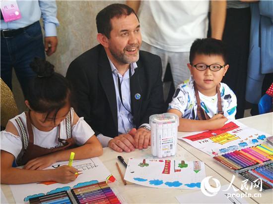 外宾在新密黄固寺村跟画画的孩子们互动 王佩 摄